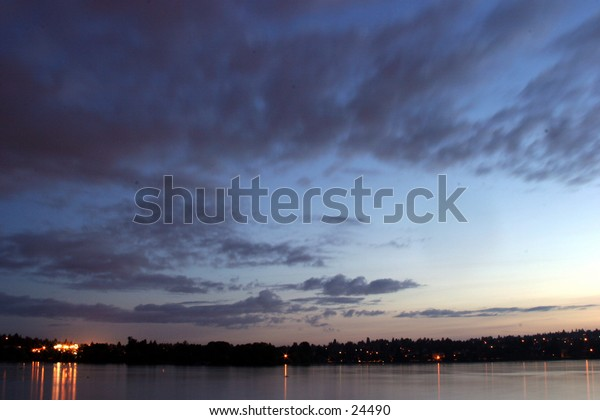 The sun slowly rises over seattles green lake creating a beautiful sky with whispy clouds