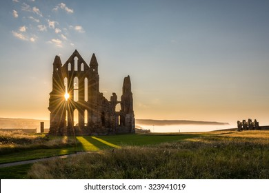 Sun Star on Whitby Abbey / The Gothic ruins of Whitby Abbey with the suns rays producing a star.  Sea mist held back by the cliffs at Sandsend in the background