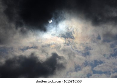 Sun in Stormy Sky - Photograph of the sun coming out from behind dark clouds, causing some iridescence in surrounding clouds.
