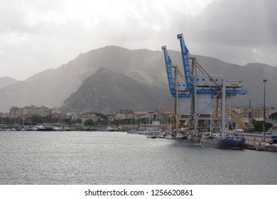 Sun streaming through clouds on the harbor of Palermo, Sicily, Italy