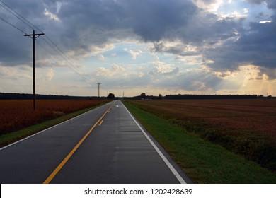 The sun streams between the rain clouds over rural farmland in eastern North Carolina.