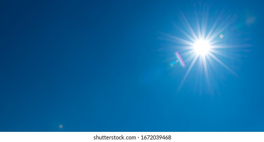 Sun, sunbeams against blue sky - cloudless sky. Photography with Lense flair effect
