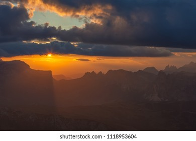 Sun at sunset between clouds and spectacular Dolomite peaks of Sella Pass, Lagazuoi, Dolomites, Italy