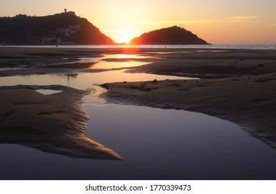 Sol al atardecer frente a la playa de La Concha en la ciudad de Donostia, San Sebastián, Euskadi