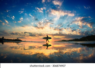 Sun surfer. A man is walking with a surf in his hands across the sea shore.  - Shutterstock ID 306874907