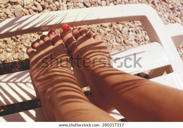 Sun tanned female legs under palm shadow