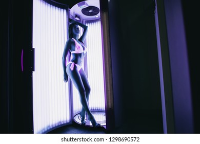Sun tanning. Sexy beautiful girl sunbathing in the solarium in neon light