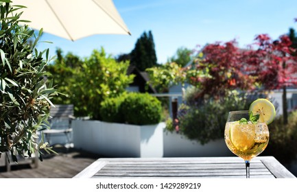 Sun terrace with cold summer drink on a wooden table