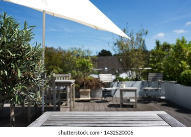 Sun terrace with empty wooden table for recreation