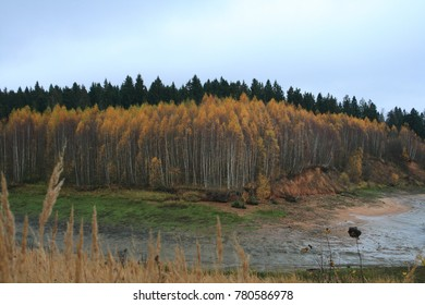 Sun through clouds in an autumn day. Forest-covered hills near Kunya river, a water reservoir of hydroaccumulating power plant in Bogorodskoe, Sergiev Posad district, Moscow region.