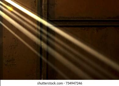 Sun through cracks. Horizontally. Light beams penetrate through the holes in the old iron gate.