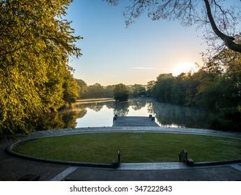 Sun through tress with reflections in lake in Botanical Gardens, Atlanta