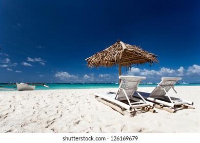 Sun umbrella with chair longues on tropical beach, Philippines, Boracay