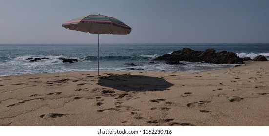 Sun umbrella in empty beach of Forte do Paco.