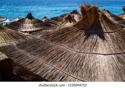 Sun umbrella on exotic Croatian beach resort. Comfortable parasol on the Adriatic seaside. Travel destination for summer vacation cruise