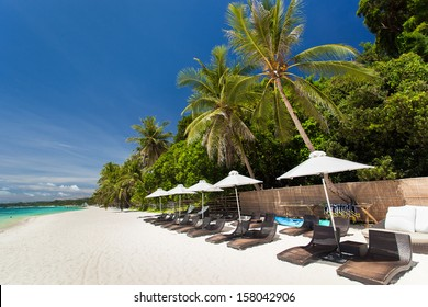 Sun umbrellas and beach chairs on tropical coast, Philippines, Boracay