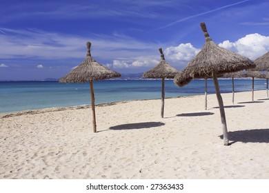 Sun umbrellas on the beach in Mallorca Spain