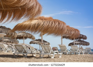 A lot of sun umbrellas on a beach, with a view of a horizon line over the sea, sky, a symbol for holiday vacation