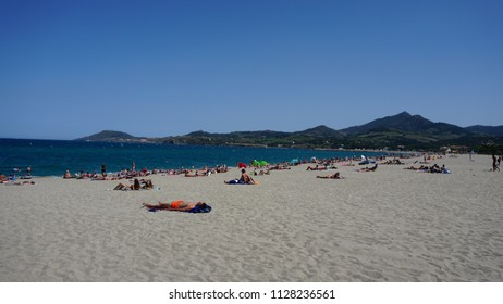 Sunbathers lying on sandy beach in Argeles sur Mer in France with clear blue skies and green hills in the distance June 2018