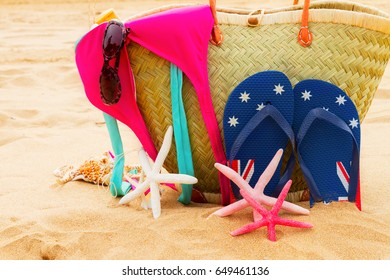 sunbathing accessories in straw bag close up on sandy beach by the sea