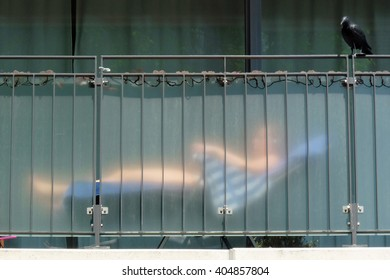 Sunbathing behind a translucent balcony balustrade
