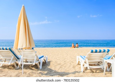 Sunbathing on resort beach on hot, sunny day. Umbrellas and sunbeds on white sand against the blue sea and clear sky. Two women sit on sand and relax near sea