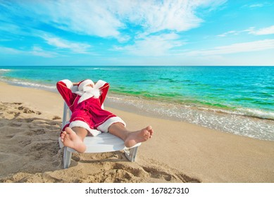 sunbathing Santa Claus relaxing in bedstone on tropical sandy beach - Christmas concept
