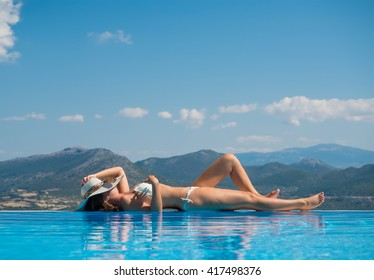 Sunbathing woman relaxing under sun in luxury. Woman lying on her back on wet sand in front of the ocean at the seaside