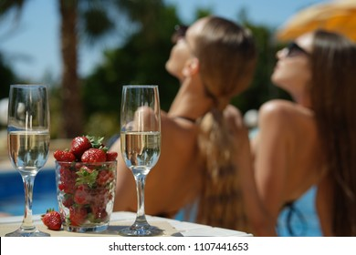 Sunbathing women near swimming pool, strawberry and sparkling wine