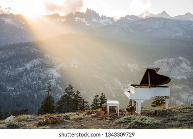 A sunbeam falls on a piano, which is positioned on a mountainside at Minaret Vista near Mammoth Mountain, California. The Minarets are in the background.