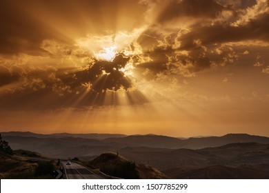 Sunbeams breaking through clouds at sunset. Red sky over hill and mountains.  Dramatic heaven. Travel concept. Car travel adventures.