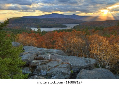 Sunbeams escape the clouds at sunset on sunset rock in the Autumn, overlooking North-South Lake in the Catskills Mountains of New York.  HDR image.