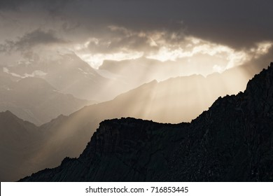 Sunbeams falling at the beautiful valley with rocky mountain ranges in Swiss Alps right after the heavy rain