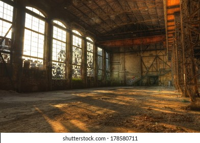 Sunbeams falling through large window in an abandoned industrial hall