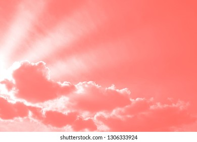 sunbeams lighting through clouds, living coral tone