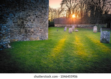 sunbeams, rays through trees onto green grass in a graveyard by a stone church wall with old worn tomb stones.