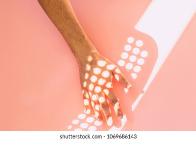 sunbeams reflected on the hand and a pink wall. minimal and surreal creative concept