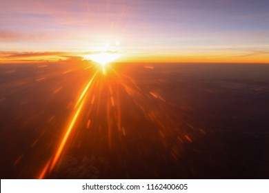 Sunbeams shining, sun rays during sunrise. View from airplane window above the clouds with blue sky and cloudscape in sunlight morning.