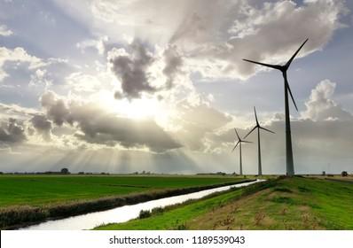 sunbeams in stormy sky over wind turbines, Holland