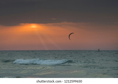 Sunbeams upon a wind surfer during sunset