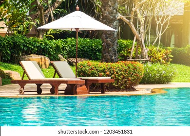 Sunbed with beach umbrella on side of swimming pool with garden view. Relaxing facility for summer vacation activity.