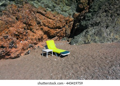 Sunbed on the beach in front of rock