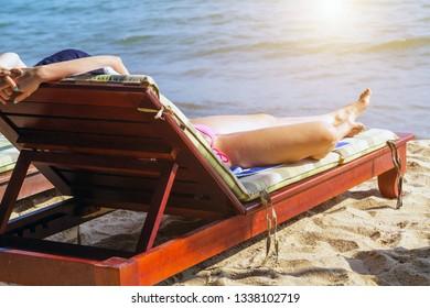 Sunbed woman tanned body bikini sunbathing on deck chair, relaxing on beach chair Caribbean travel Vacation.