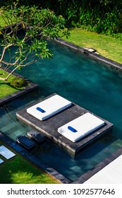 Sunbeds by the pool in lush, tropical setting, Bali, Indonesia