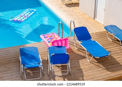 Sunbeds by a swimming pool in sunny day. Vacation, summer and relax.