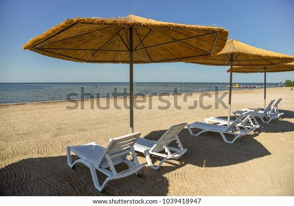 Sunbeds and cane umbrellas on sandy beach
