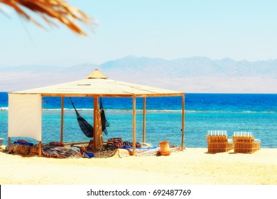 Sunbeds, hammock & simple tent at sandy beach by the seaside. Red Sea in Egypt (Nuweiba bedouin village). Bright summer sunny colors. Tranquil & chilling out day.