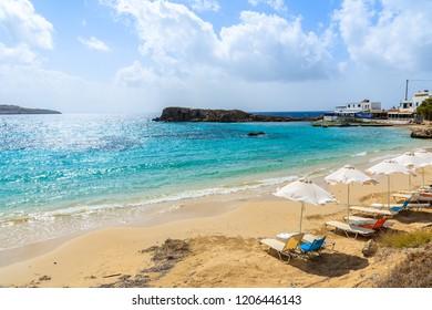 Sunbeds on beautiful beach in Lefkos village on coast of Karpathos island, Greece.