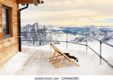 Sunbeds on the terrace of the Alpine Chalet house in the mountains. Winter vacation in Alps .