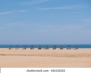 Sunbeds and sunshades lined up in a row in Isla Canela beach, Ayamonte, Andalucia, Spain. soft sand and a blue sky can be seen with the horizon of the sea.